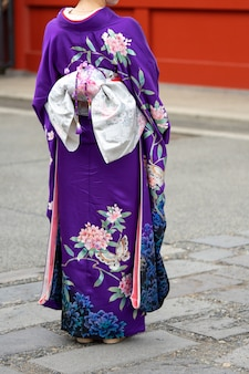 日本の東京の浅草寺の前に日本の着物姿で立っている若い女の子