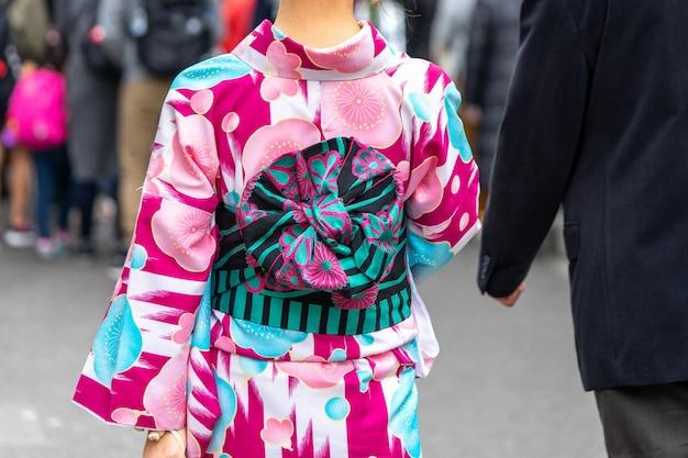 東京の浅草寺の前に日本の着物姿の地位を着た少女