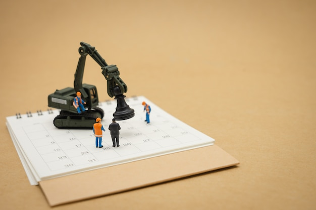 白いカレンダーとミニチュア人建設労働者修理