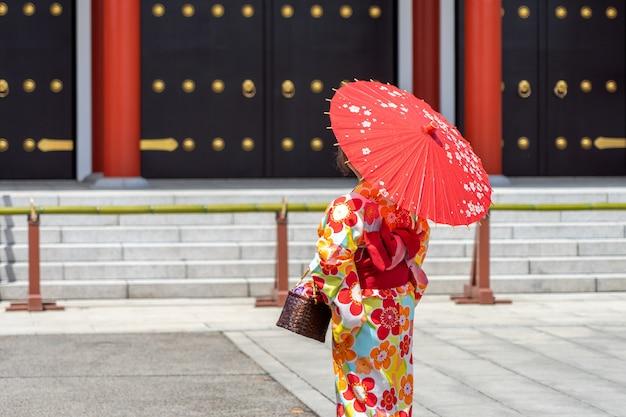 東京の浅草寺の前に日本の着物姿で身に着けている若い女の子、