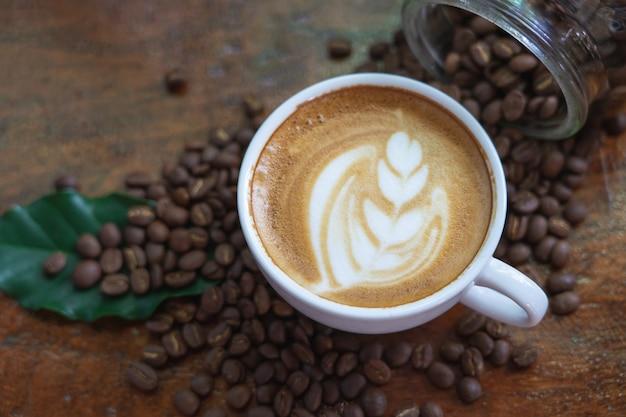 Белые кофейные кружки и кофейные зерна. вылил на красиво оформленный деревянный стол
