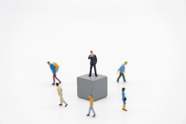 白いジグソーパズルの上に立ってミニチュア人ビジネスマン。