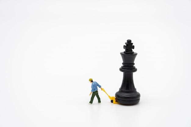 背面にチェスの駒を持つミニチュア人建設労働者。
