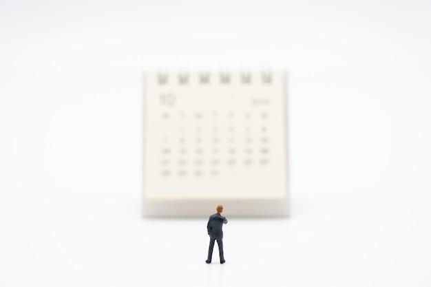 白いカレンダーの上に立ってミニチュア人ビジネスマン