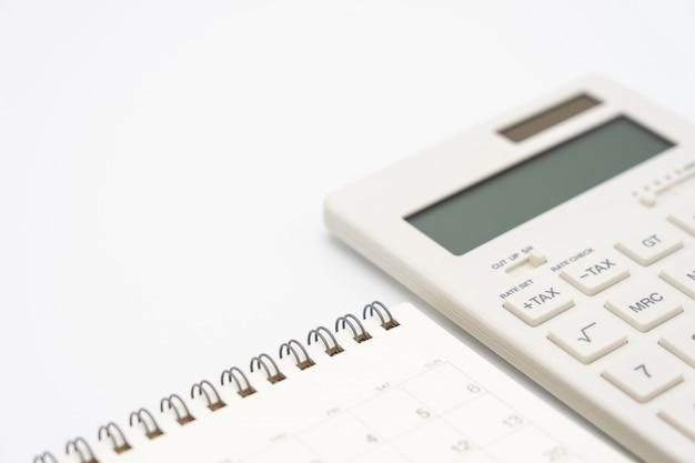 カレンダー、電卓ペンおよび他のオフィスのあるトップビューオフィステーブルデスクのフラットレイアウト