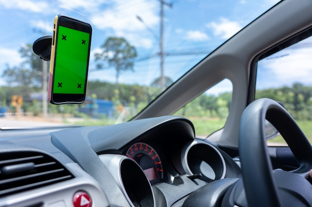 アジア人の若者が町と緑の空白の画面を持つスマートフォンで車を運転します。
