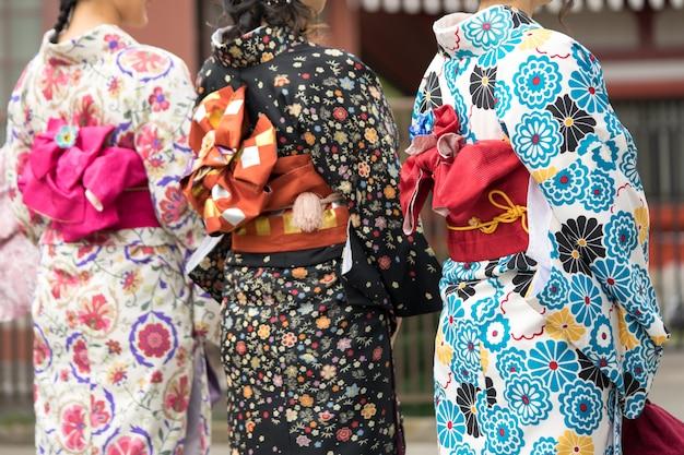 日本の東京の浅草寺の前に日本の着物姿で立っている若い女の子。着物は日本の伝統的な衣服です。言葉