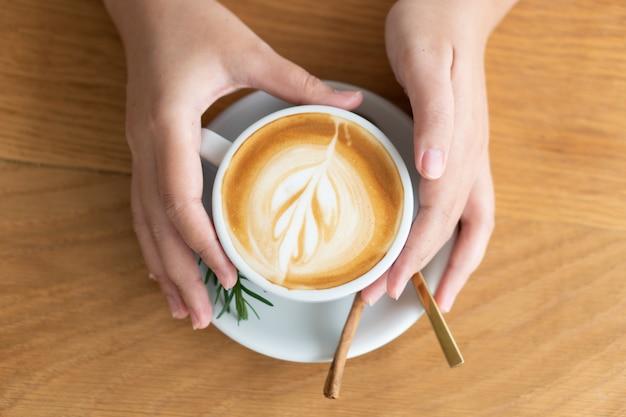 白いコーヒーのマグカップを持つ女性の手。コーヒーはラテです。木製のテーブルの上のテーブル
