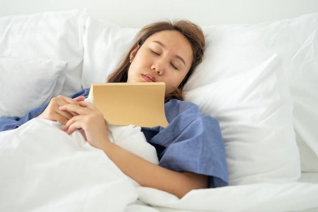 Азиатская девушка читать книги во время сна.