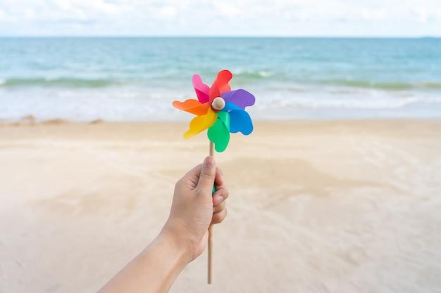 カラフルな風車の紙がビーチに刺繍