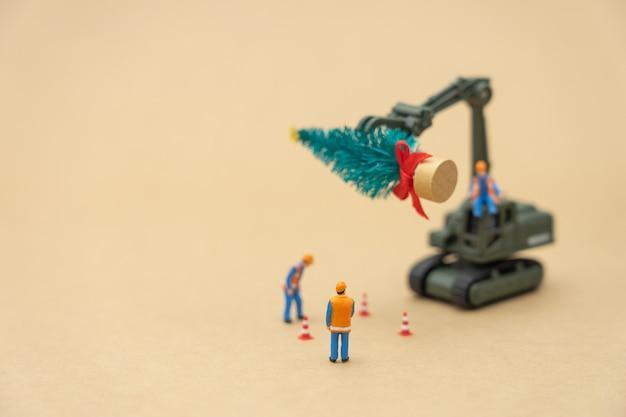 ミニチュアの人々クリスマスツリーの上に立っている建設労働者