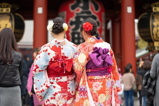 東京の浅草寺の前に立っている日本の着物を着た少女。