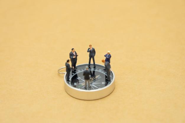 ミニチュアの人々のビジネスマンは、背景戦略としてコンパスの地位を分析します