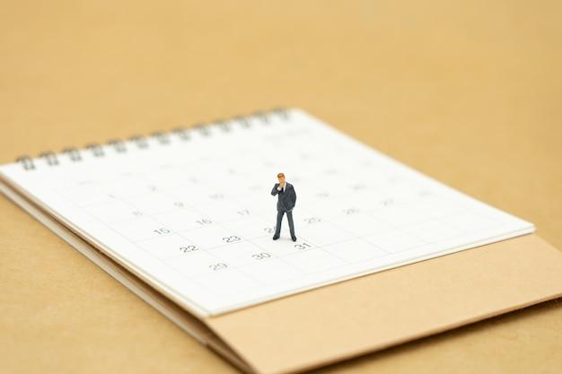 白いカレンダーの上に立っているビジネスマンのミニチュア