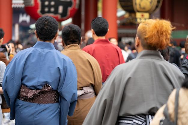 日本の東京の浅草寺の前に立っている日本の着物を着た少女。