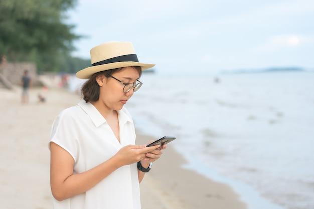 スマートフォンを保持している美しい若い女性