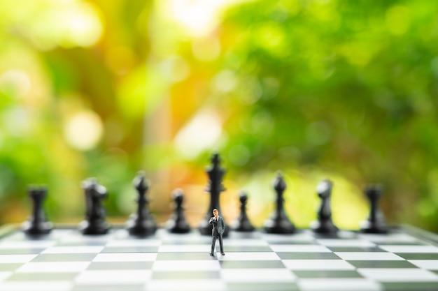 チェスの駒を背負ってチェス盤の上に立っているミニチュアのビジネスマン