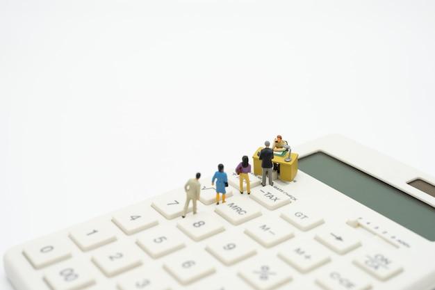 Миниатюрные люди оплачивают очередь годовой доход (налог) за год на калькуляторе.
