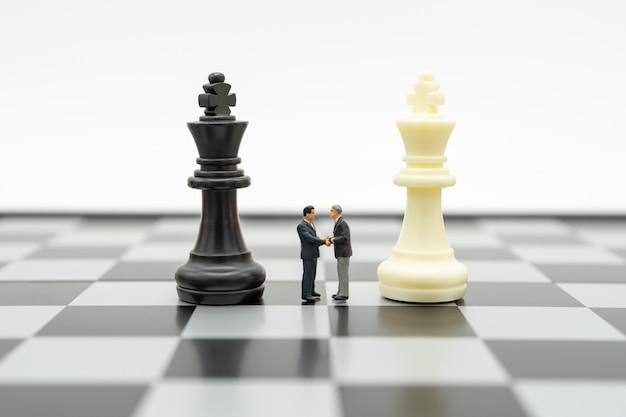 Миниатюрные люди бизнесмены пожимают друг другу руки стоя на шахматной доске с шахматами