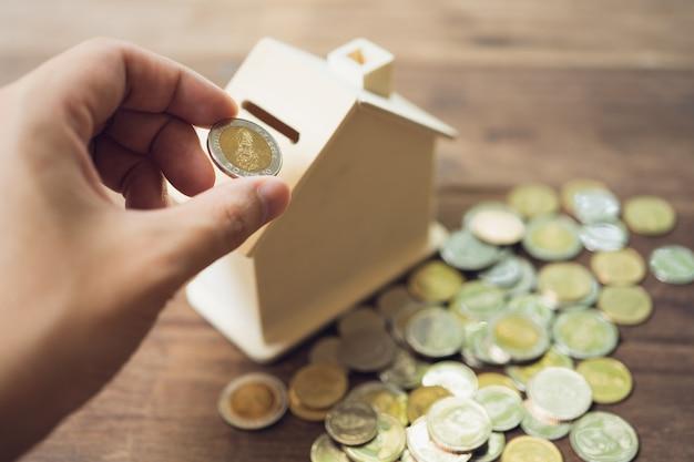 貯金箱の中にコインを置く手