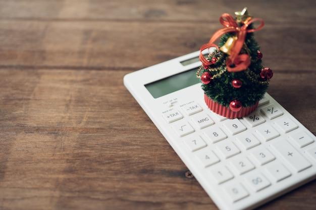 白い電卓とミニチュア本の上に置かれた美しく装飾されたクリスマスツリー。