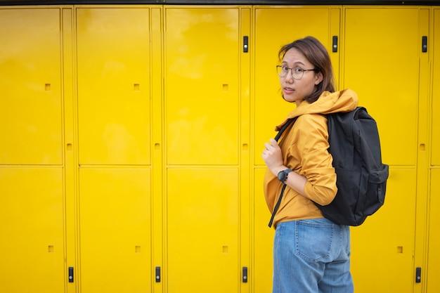 Азиатские туристы стоят перед автоматической камерой хранения багажа.