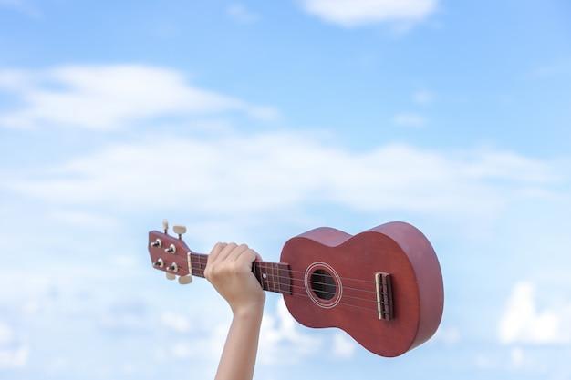 バックグラウンドでギターを持っている女の子の手は明るい空で、気持ちを与えます