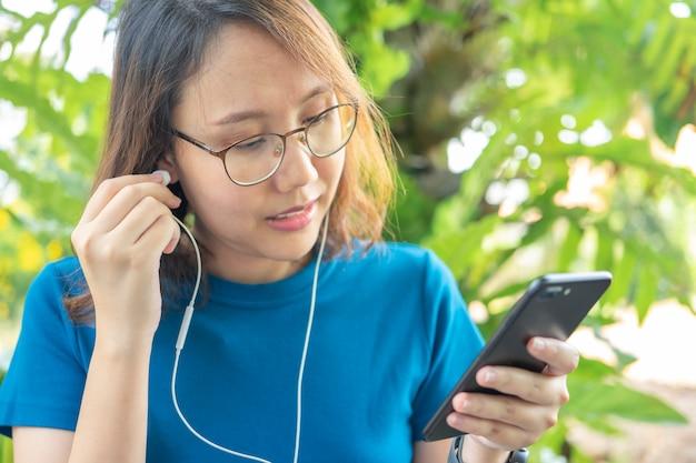 スマートフォンを持った美しい女性楽しさと笑顔ソーシャルメディアタイプのテキストメッセージ、