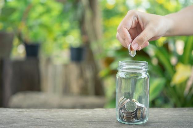 ビジネスマンはコインをガラスの瓶に入れます