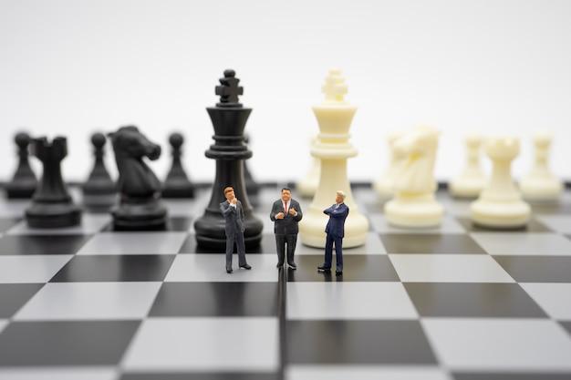 チェスの駒をチェス盤の上に立っているミニチュアの人々ビジネスマン