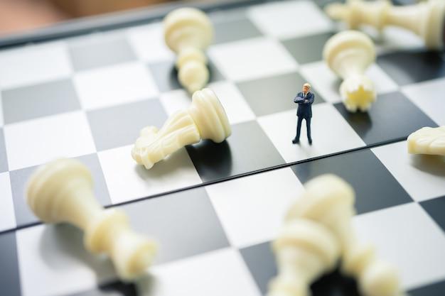 Миниатюрные люди-бизнесмены стоят на шахматной доске с шахматной фигурой