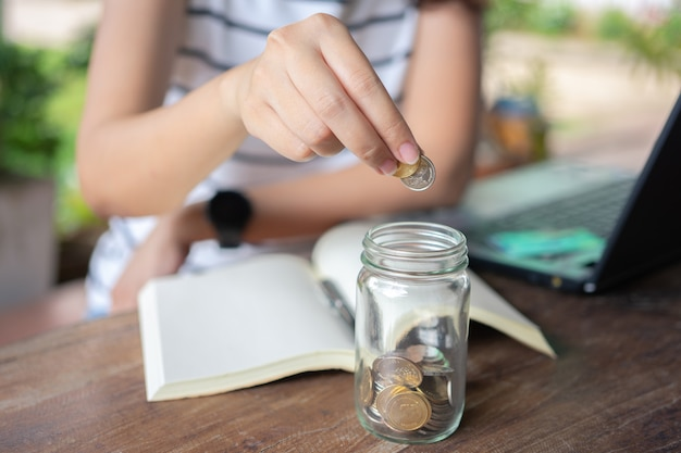 Деловая женщина положила монету в стеклянную банку, чтобы сэкономить, сэкономить