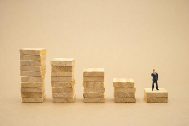 投資分析または投資に立っているミニチュアの人々のビジネスマン。
