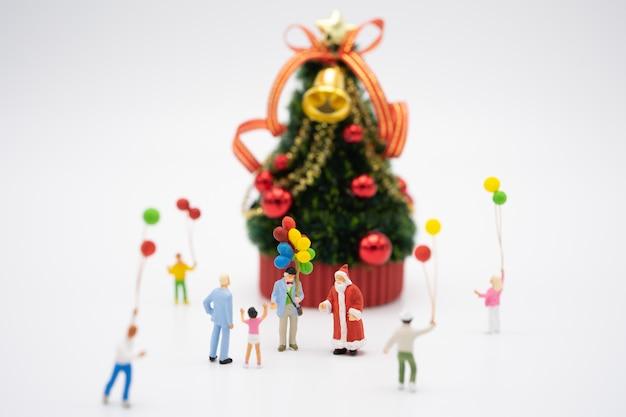 クリスマスツリーの上に立って家族ミニチュアの人々がクリスマスを祝う