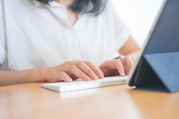 Молодой фрилансер или бизнесмен, работающий на дому в офисе и набрав на клавиатуре