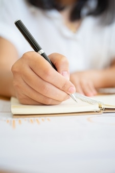 何かを書くペンを保持している実業家の手のショットを閉じる