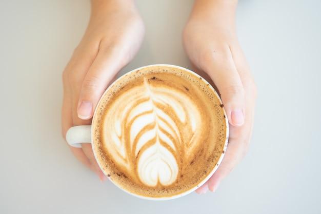 白いコーヒーマグカップを持つ女性の手。コーヒーはラテです。
