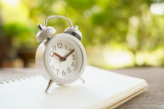 木のヴィンテージの白い目覚まし時計。休憩の時間です。