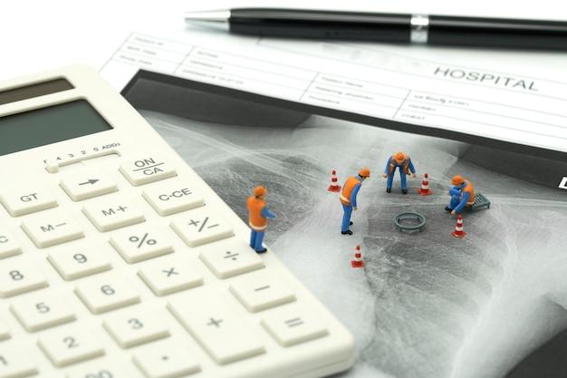 Миниатюрные люди строительный рабочий на белом калькуляторе с рентгеновским снимком легких