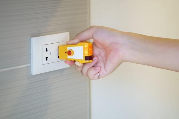 壁のコンセントにプラグをチェックするための電気テスターを持っている手。品質を確認する