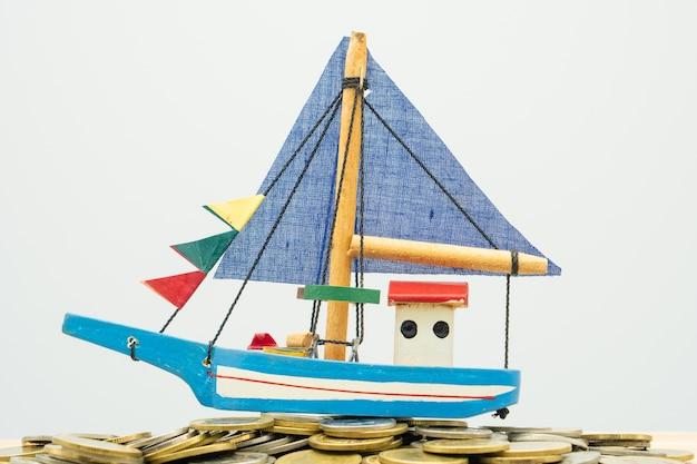モデルボートは、背景のビジネスコンセプトとしてのコインの山に置かれます。