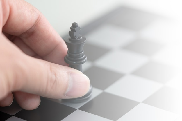 キングチェスを持っているビジネスマンは、チェス盤に置かれています。