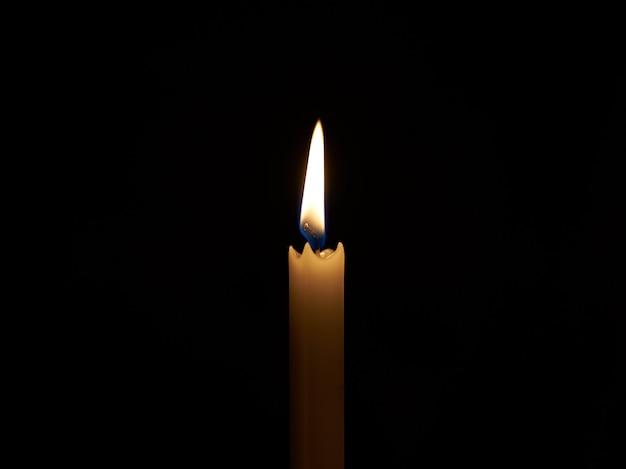 暗い部屋のキャンドルからの炎。生き残る手段の光。