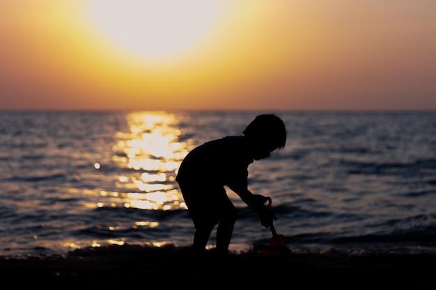 シルエット少年はビーチの砂の城を演奏しています。日没時に楽しもう
