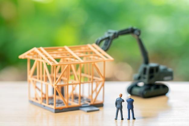 投資分析住宅または投資を立てるミニチュアビジネスマン