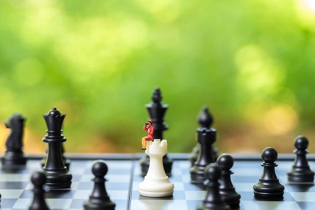 チェスの分析に座っているミニチュアの人々のビジネスマンは、