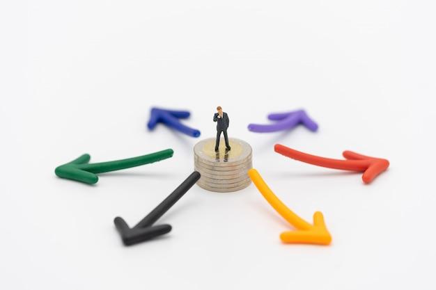 投資分析または投資を立てるミニチュアの人々のビジネスマン