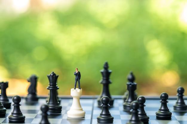 チェスの分析を立てるミニチュアのビジネスマンコミュニケーション