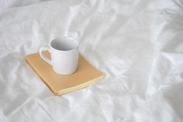 ノートブラウンカバーに置かれた白いセラミックコーヒーマグ。