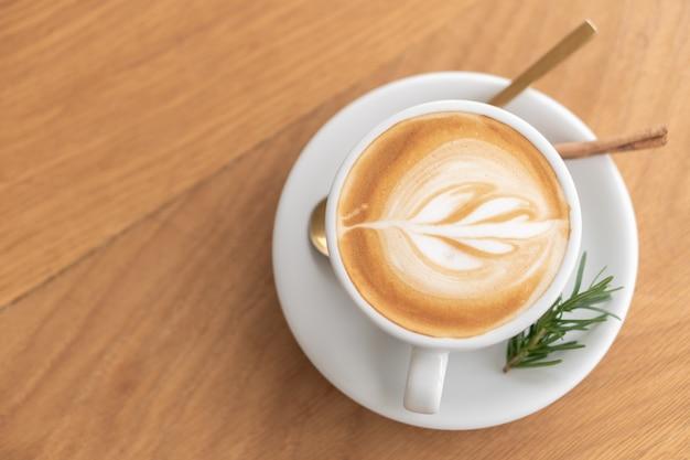 白いコーヒーマグ。コーヒーはラテです。ヴィンテージスタイルの木製テーブルのテーブル
